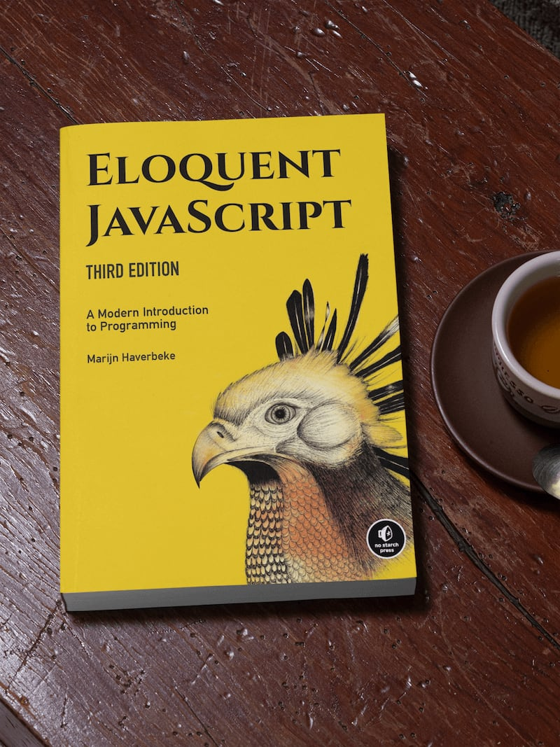 Thick paperback copy of Eloquent Javascript on a rustic table next to a cup of coffee.