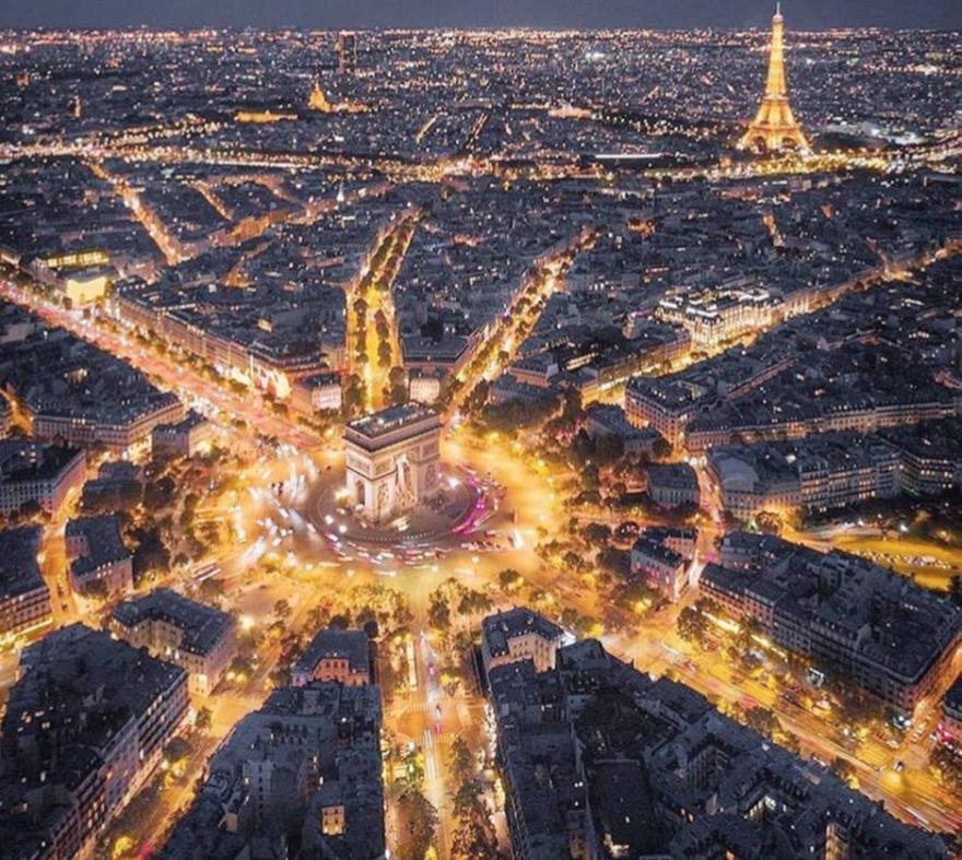 Aerial view of Paris at night, with orange-illuminated streets around the Arc de Triomphe