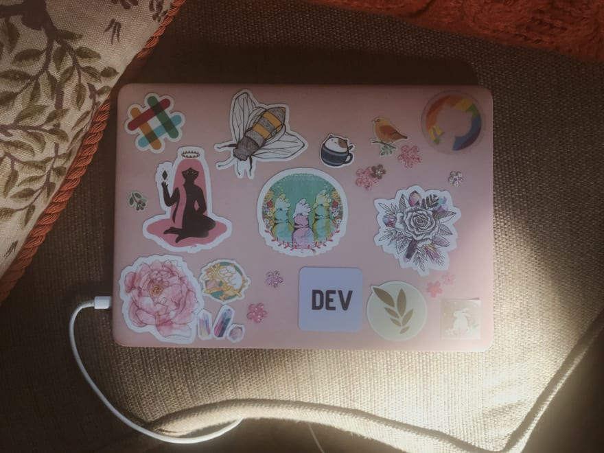 my laptop, a macbook pro in a pink case sprinkled with pastel stickers