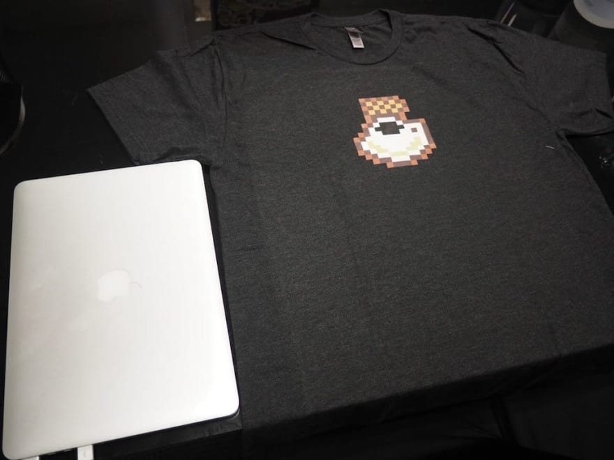 The pixelated KopiJS t-shirt, besides a Macbook for size comparison