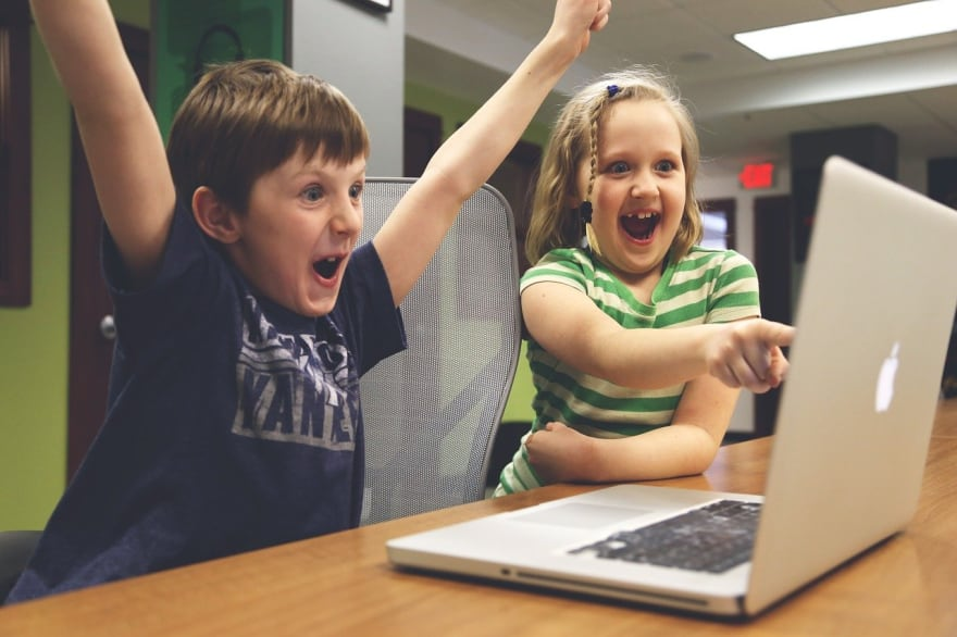 Children pointing at a laptop screen and celebrating