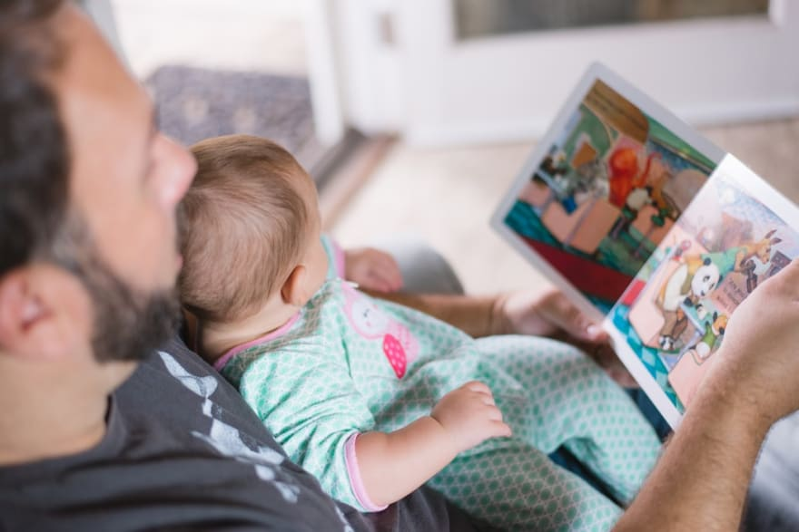 Person with baby on lap reading a children's book to the baby
