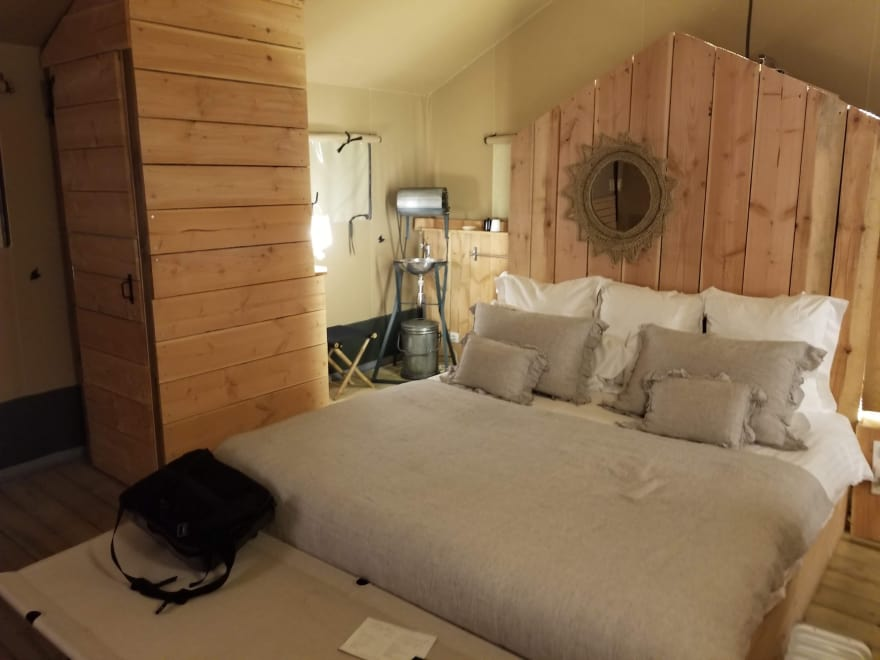 King-size bed in a rustic wood and canvas room.