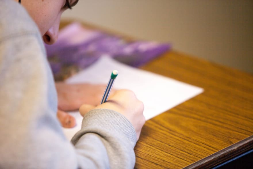 Image of a student with a mechanical pencil taking a test.