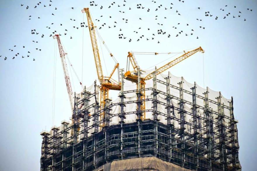 Cranes on top of big building under construction.