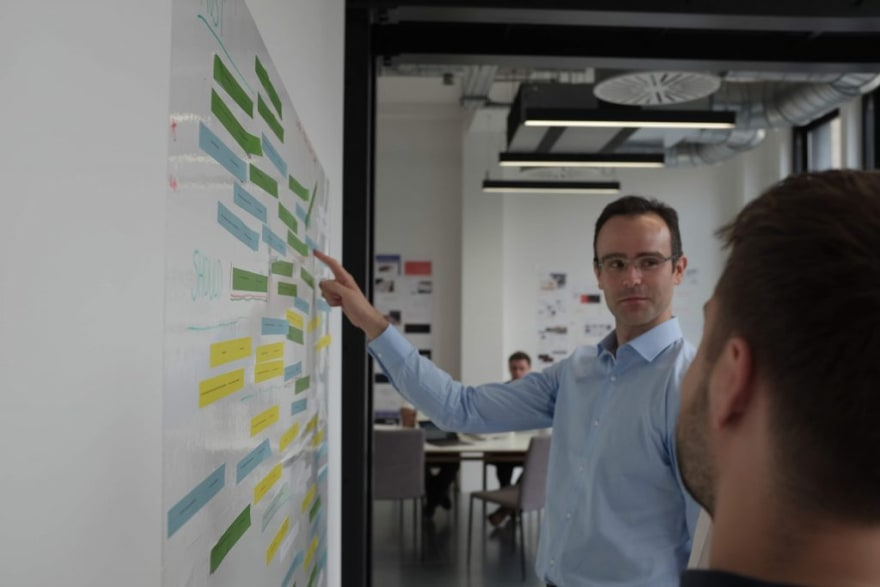 Two people order product feature cards on a wall as part of a research exercise