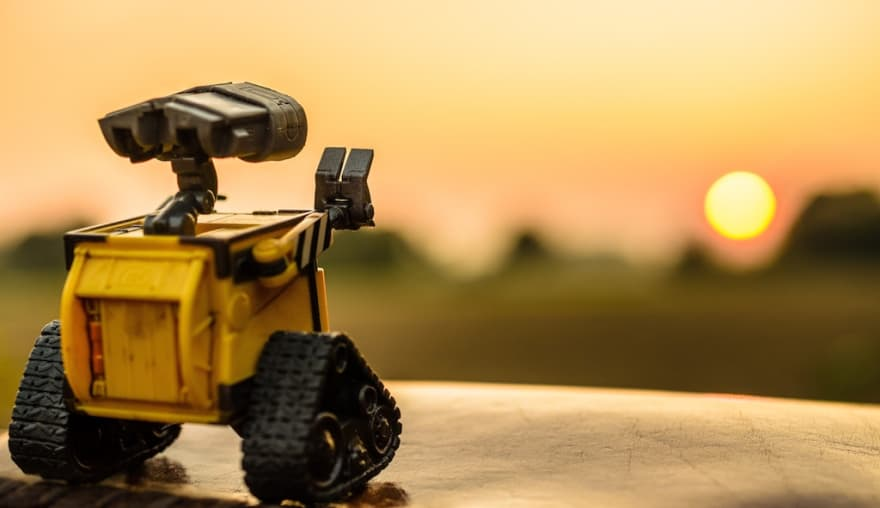 Image of Wall-E robot waving at sunset.