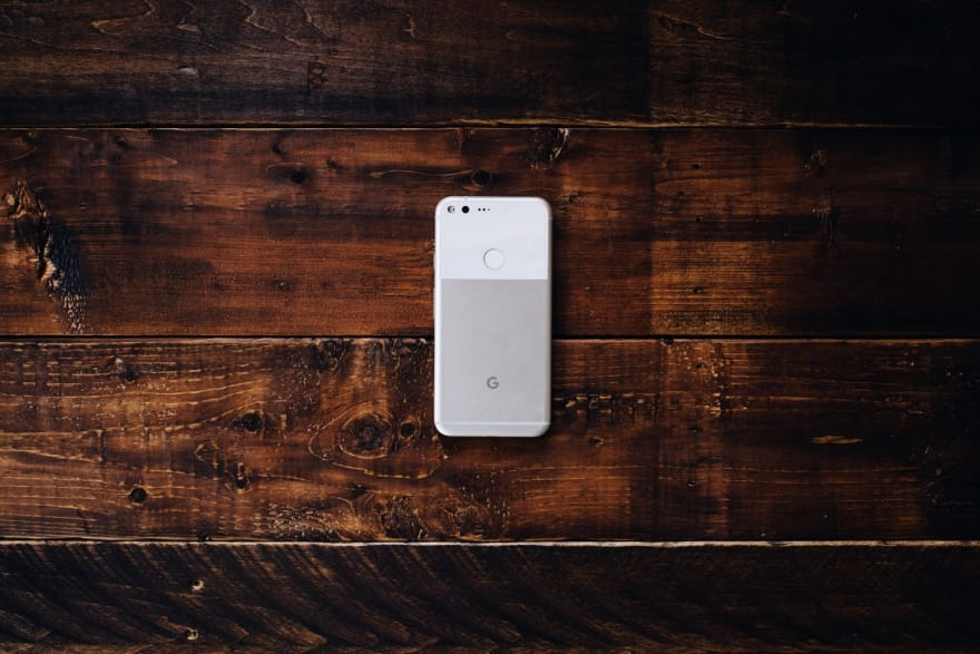 The back of a Google Pixel XL in the Very Silver color, laying on darkly stained wooden table