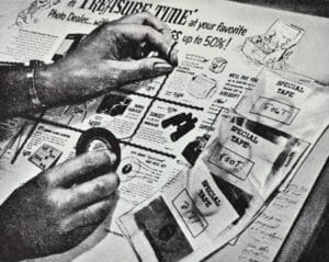 Monochrome image of someone's hands laying decorative tape between paste-up elements on a newspaper advertising page