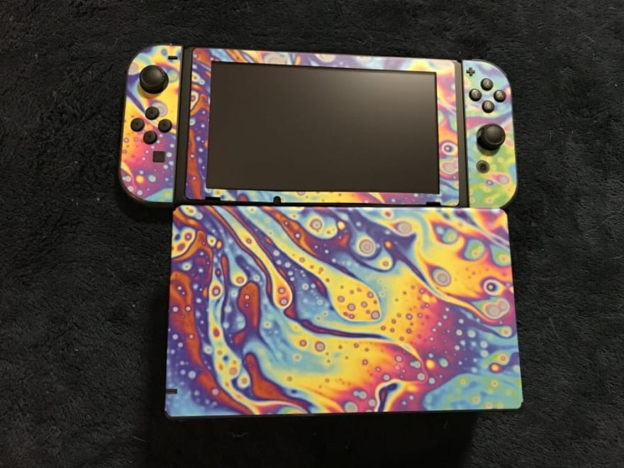 A Nintendo Switch with a colorful soapbubble vinyl skin