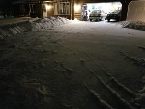 A shoveled driveway, by the light of the garage door