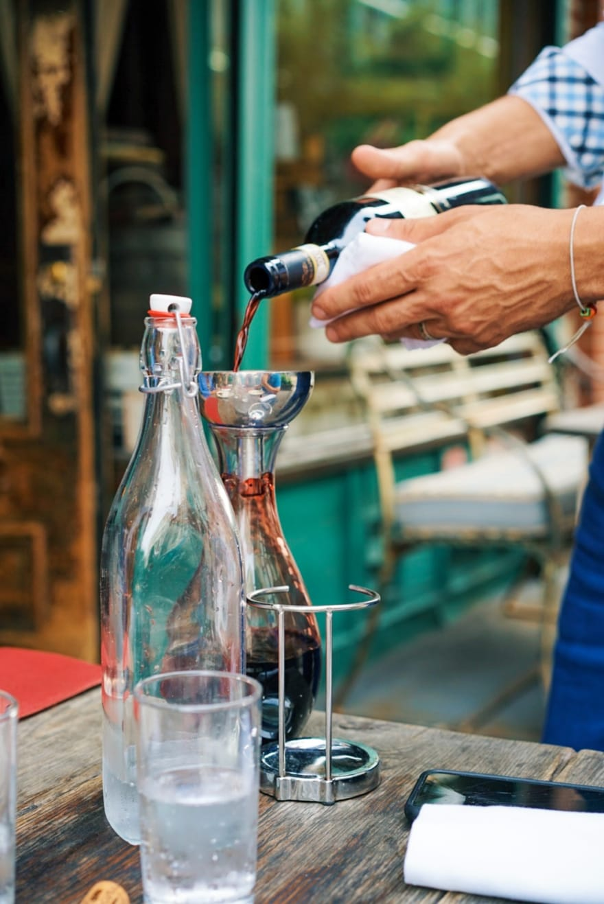 Bottle of wine being poured into a decanter