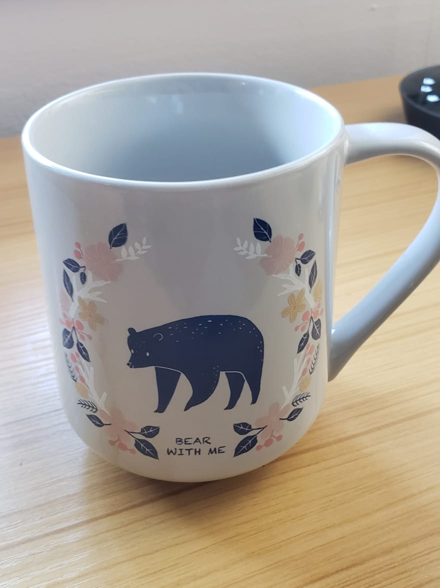 A coffee mug with a picture bear surrounded by foliage saying Bear With Me