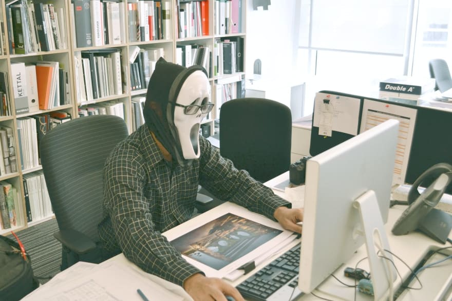 Person wearing halloween mask from the movie Scream sits at a computer