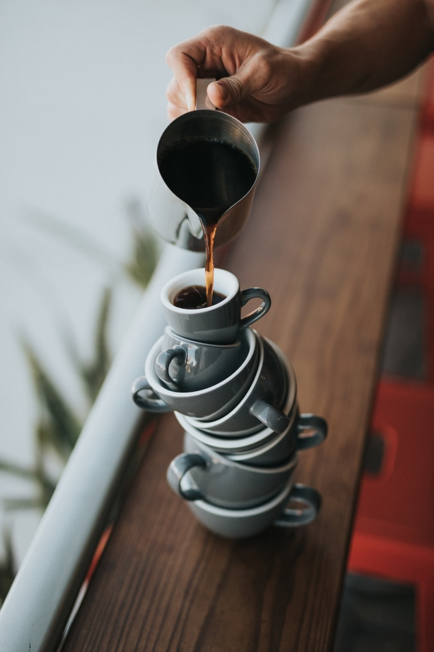 Coffee being poured into a stack of mugs