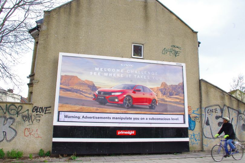 "Billboard vandalised with ""Warning: Adverts may manipulate you on a subconscious level"""