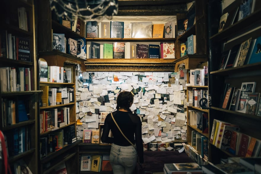 Woman in a book store staring at a wall covered in notes