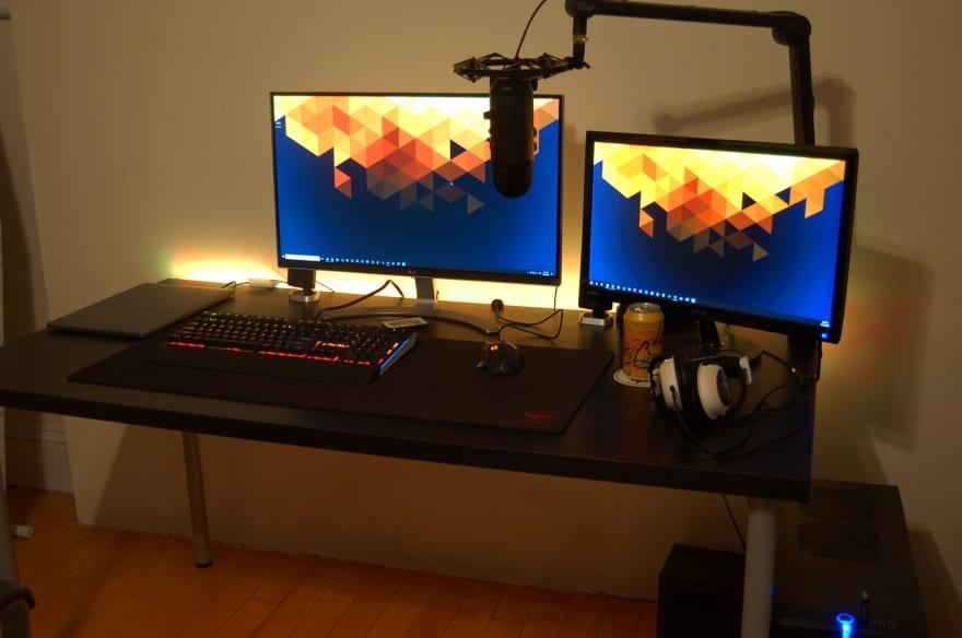 desk with 2 monitors, orange lights, and an orange seltzer