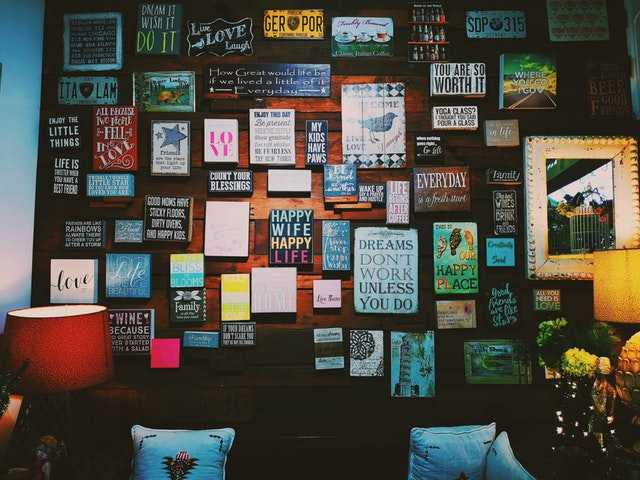 Wall with various inspirational quotes and pictures hung on it