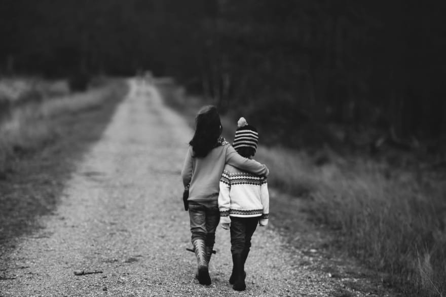 Image of two children walking down a road. One child has their arm around the other