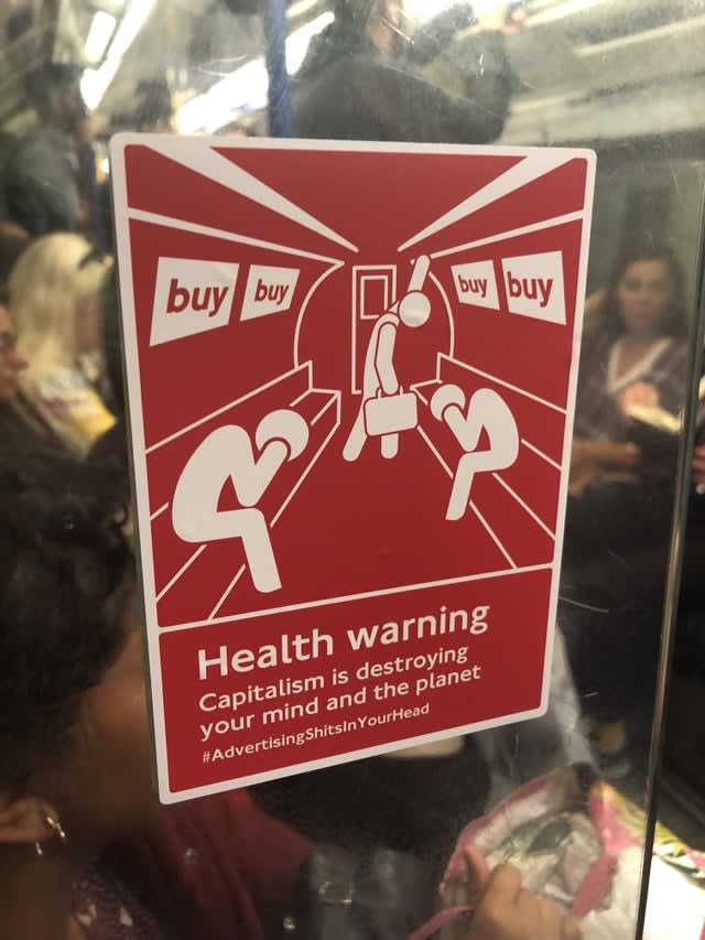 "Sign on the tube reads: ""Health warning! Capitalism is destroying your mind and the planet hashtag Advertising Shits In Your Head"