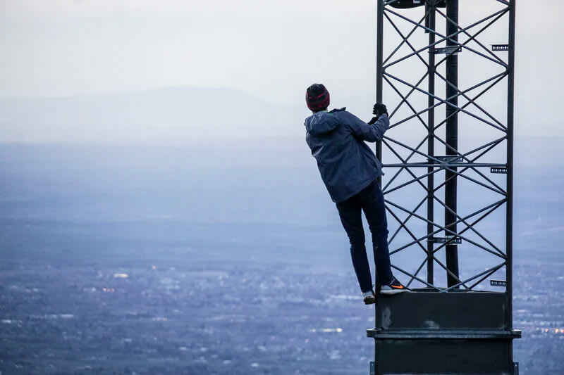 person holding onto cell tower