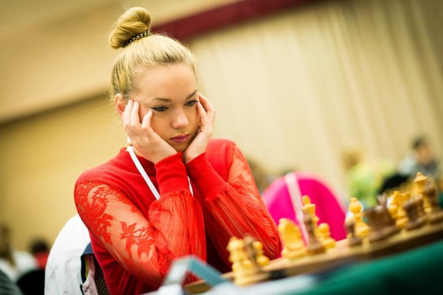 woman playing chess, deciding what move to make