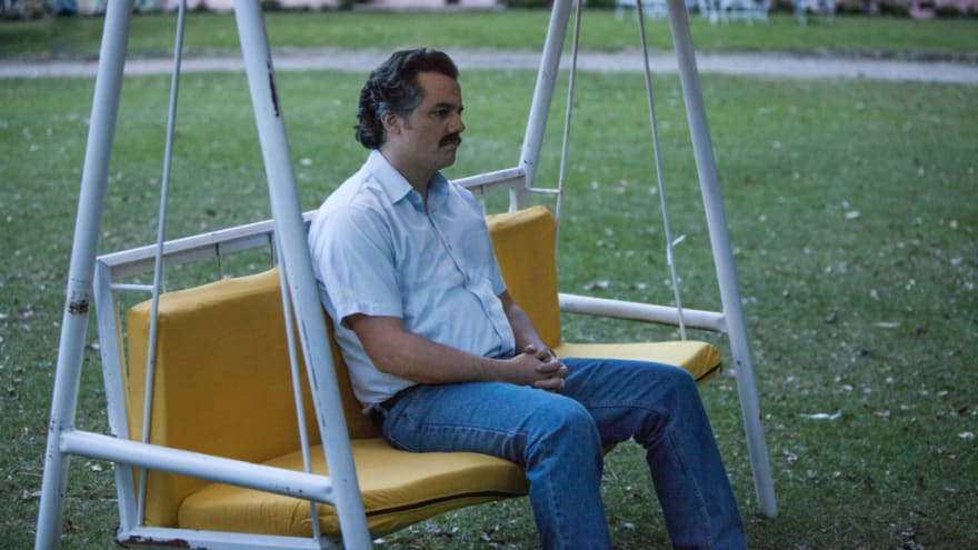 pablo escobar sitting sad on the swing