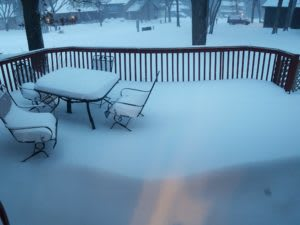 About a foot of snow covering a porch with an outdoor table and chairs
