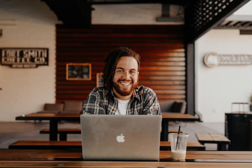 smiling man with macbook