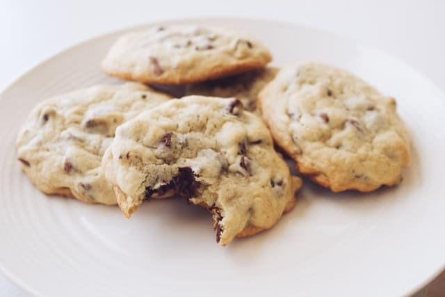 5 home-baked chocolate chip cookies piled on a plate. One has a bite out of it.
