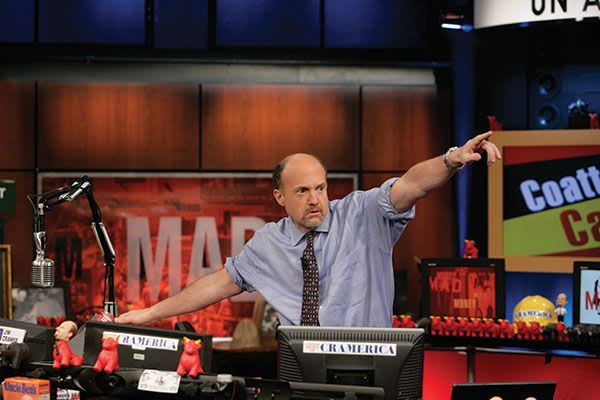 Jim Cramer sitting at a desk pointing to the sky