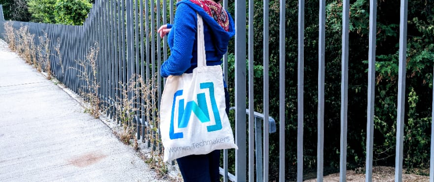A girl standing in the middle of a park with a bag with a Women Techmakers community logo on it. Photo by Celia Gómez de Villavedón.