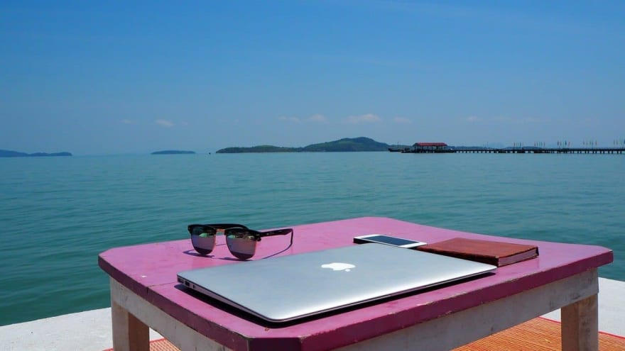 Closed MacBook in the foreground, beach in Thailand in the background
