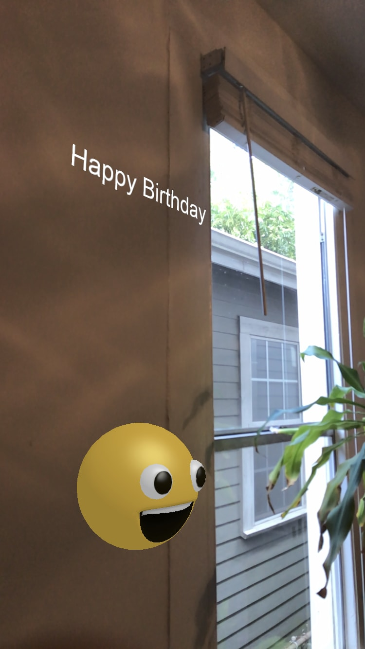 Hovering smiley face beneath Happy Birthday text from side