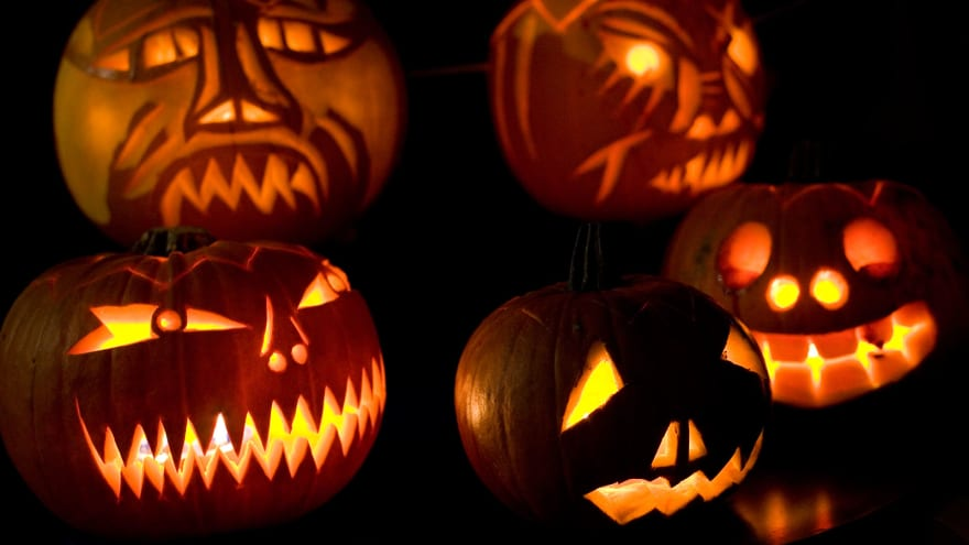 A collection of lit jackolanterns with a dark background.