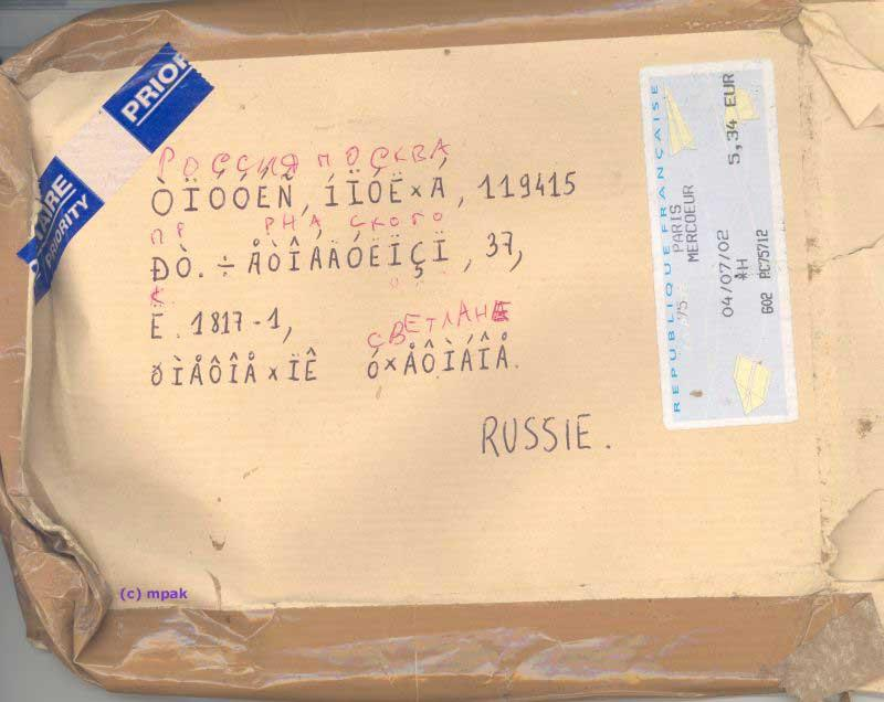 A parcel with an unreadable address handwritten in latin characters. Above each one there is a cyrillic character in red ink