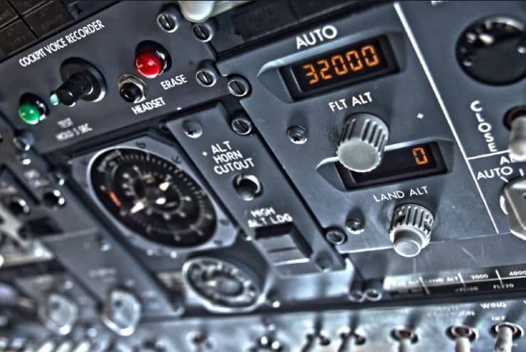 Foto do console de um avião com dezebas de pequenos botões