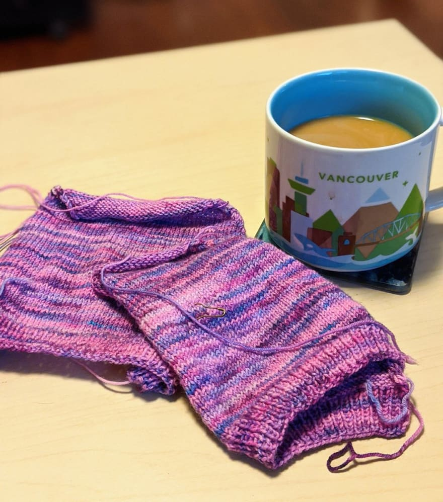 A knitting project in front of a full mug of coffee.