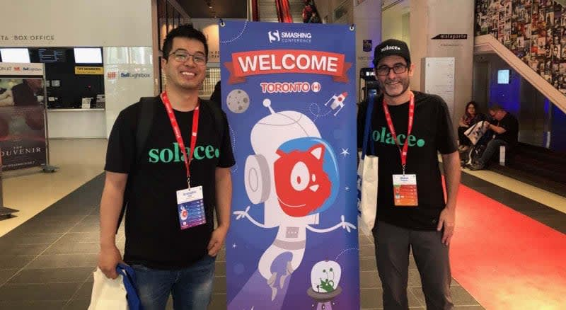 A photo of Arshabhi Rai and Blaine Hussey standing in front of the SmashingConf Toronto 2019 welcome poster