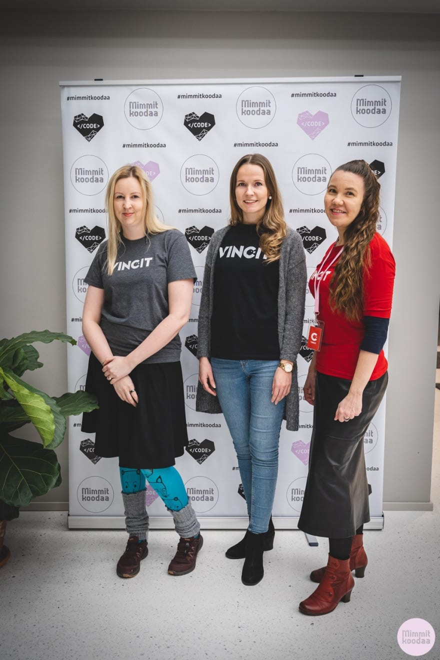 I and my two colleagues in Vincit t-shirts standing in front of Mimmit Koodaa banderol
