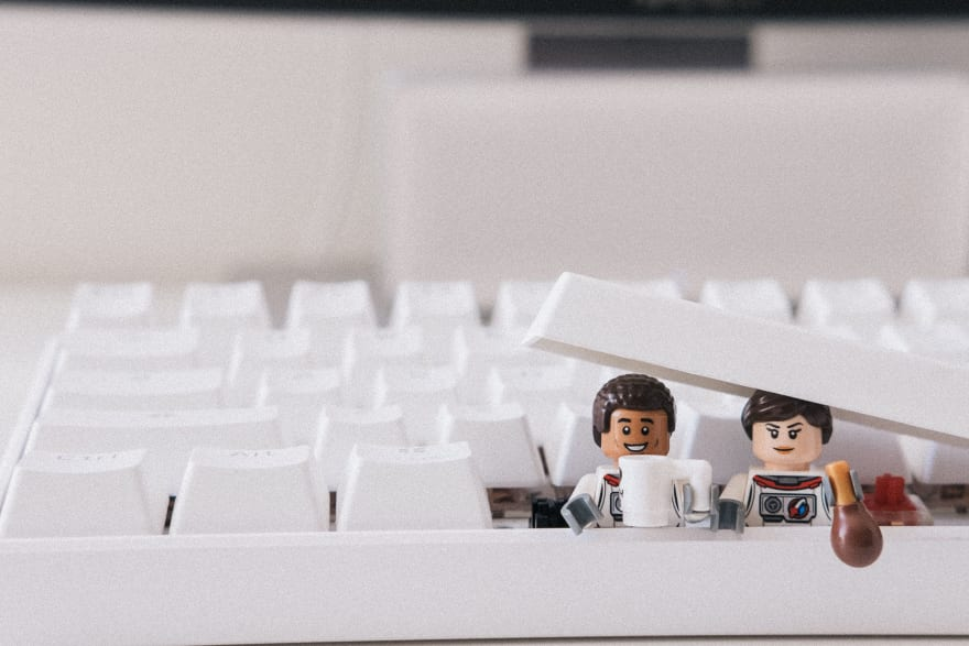 Computer keyboard with Lego characters coming out of it