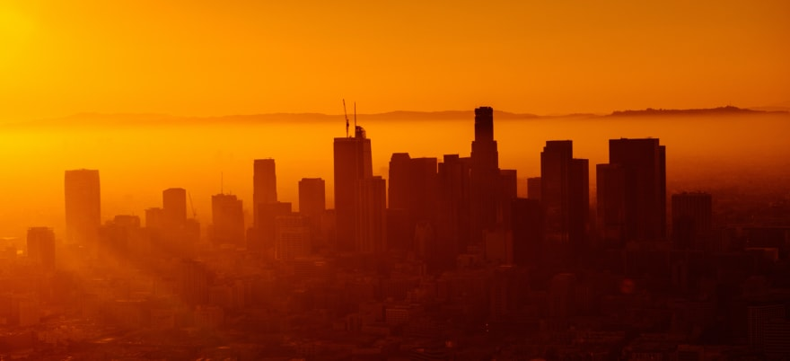 city skyline at dawn, with rays of light cutting through the morning mist by Josh Rose from unsplash.com
