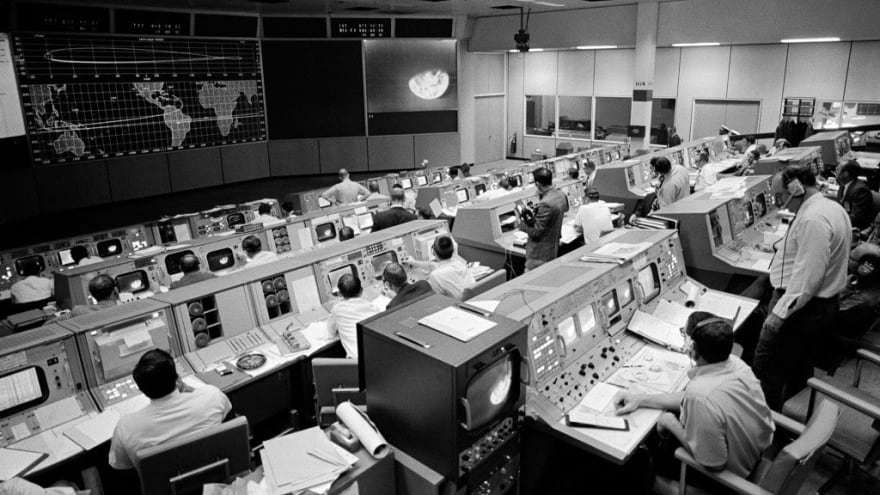 Black and white photo of Mission Control with people at their stations.