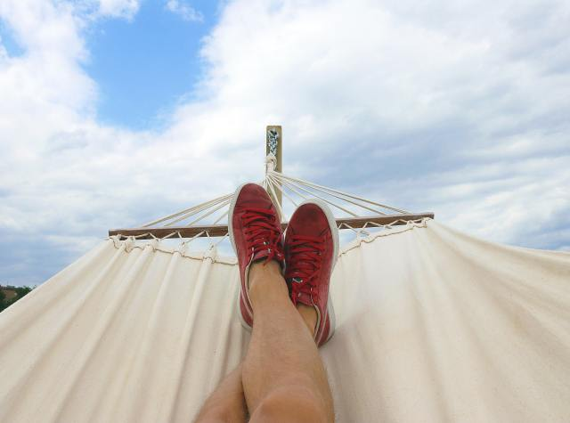 Photo of a person's legs in a hammock, picture taken from the camera-person's chest