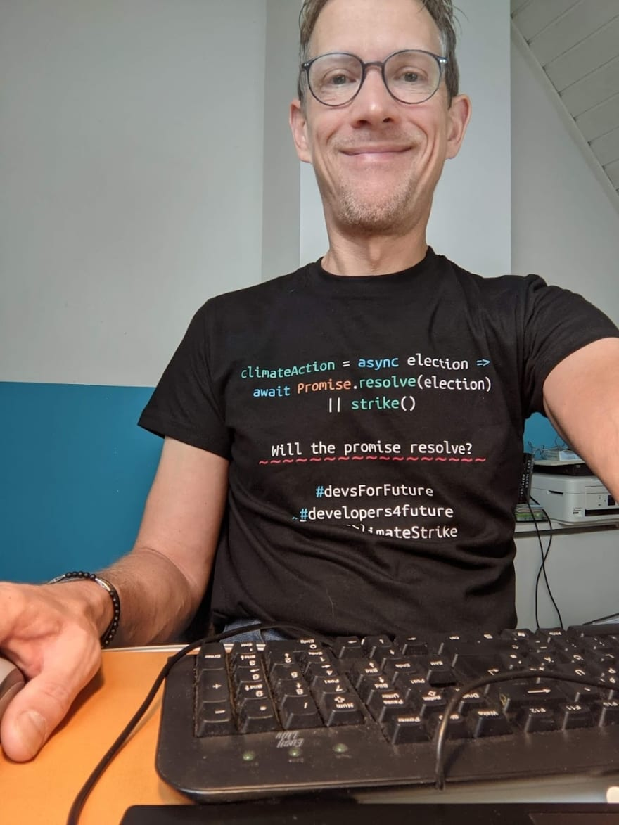 Ingo Steinke sitting at his desk in front of a keyboard wearing a t-shirt with pseudo-code: climateAction = async election => await Promise.resolve(election) || strike() Will the promise resolve? #devsForFuture #developers4future climateStrike