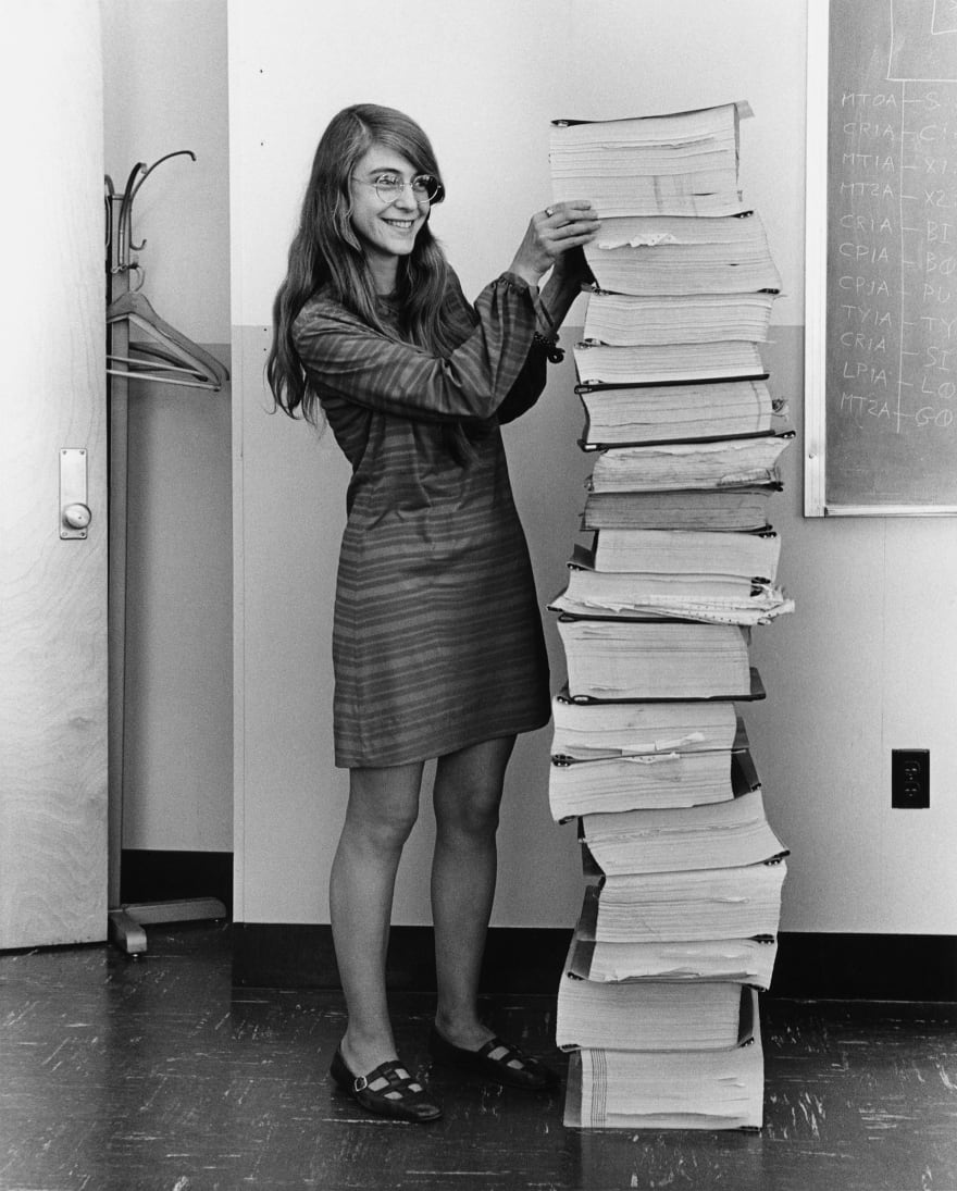 Margaret Hamilton standing next to a print out of her and her teams' code for the Apollo project