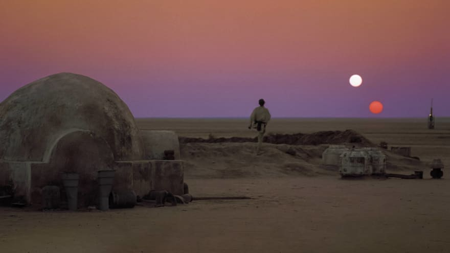 Luke Skywalker looking at the horizon at dusk of the desert planet Tatooine. Two suns are setting in the desolate landscape