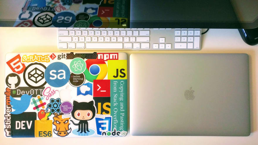 Over-head view of two Macbook laptops on a white table. Laptop on the left is covered with dev stickers, varying from JS, CodePen, React, Sass, Atom, HTML5, npm, Dev, Ladies Learning Code, and more. The laptop on the right is clean and new. Above the laptops sits an Apple keyboard and Apple monitor.