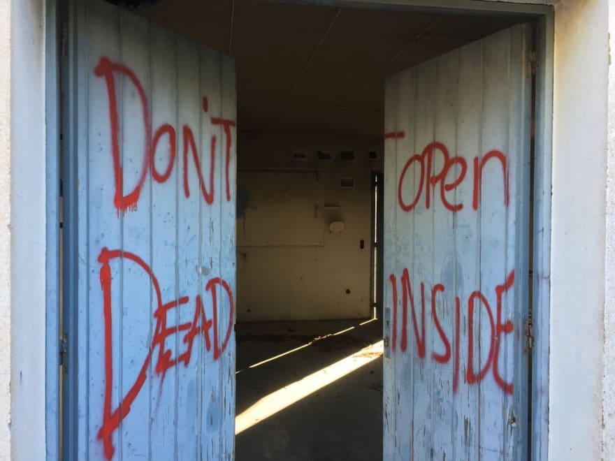 "A door with a ""Don't open, dead inside"" graffiti"
